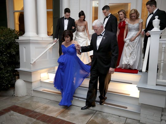U.S. Vice President Mike Pence (C) helps his wife Karen Pence down the steps of the front porch of the vice presidential residence at the U.S Naval Observatory before heading to the inaugural balls with their children January 20, 2017 in Washington, DC.