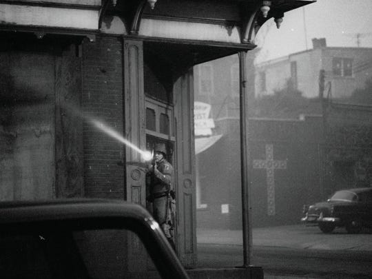 A National Guardsman surveys a street during a curfew imposed after riots following the 1968 assassination of Dr. Martin Luther King Jr.