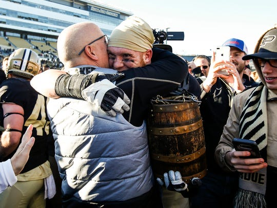 Purdue senior linebacker Garrett Hudson gets a hug while carrying the Old Oaken Bucket at Ross-Ade Stadium in West Lafayette, Ind. on Saturday, November 25, 2017. The Boilermakers beat Indiana, 31-24.