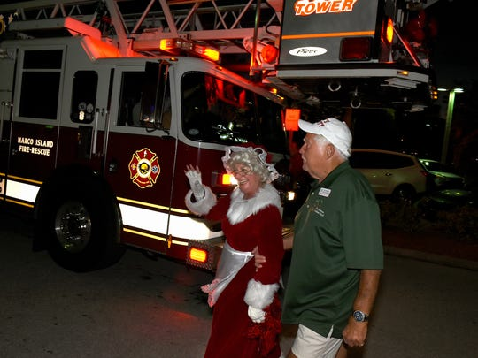 Mrs. Claus is escorted in from her fire truck. Santa and Mrs. Claus arrived Friday evening at the Shops of Marco, posing for pictures with children and officially kicking off the Christmas season.