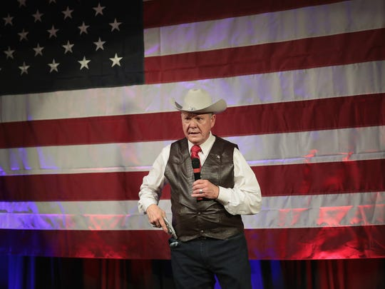 Roy Moore, displays a pistol to express his support for the Second Amendment as he speaks at a campaign rally on Sept. 25, 2017 in Fairhope, Ala.