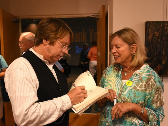 """Patrick Smith Jr., son of author Patrick Smith, signs Wendy Lindsay's well-thumbed copy. Nearly 100 people came out to the Rookery Bay Environmental Learning Center on Tuesday, Nov. 21 for a presentation on """"A Land Remembered,"""" a beloved book on Florida history."""