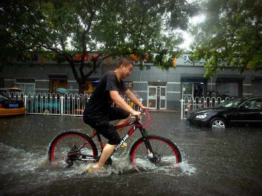 A bicyclist rides through flood waters in Beijing following heavy rain on July 20, 2016.