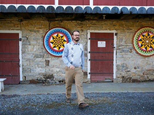Patrick Donmoyer, building conservator and exhibit specialist, walks past traditional Pennsylvania Dutch barn paintings on the barn at the Pennsylvania German Cultural Heritage Center, at Kutztown University, in Kutztown, Pa., on Nov. 28, 2017.  Donmoyer, whose family moved to Lebanon County from Philadelphia in 1732, said that approximately 400,000 people speak Pennsylvania Dutch in the United States (principally in Pennsylvania, Ohio and Indiana) and Canada. Its influence is deepest in about 14 counties in the southeastern and central parts of Pennsylvania, with thousands of residents apart from Amish and several Mennonite communities.   (Jessica Griffin/The Philadelphia Inquirer via AP)