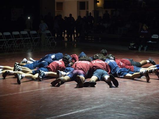 La Quinta wrestling huddles before their match against