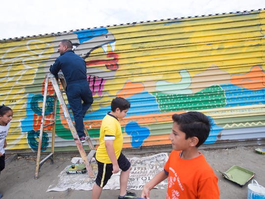 Volunteers paint the border wall separating Mexico and the U.S. in Tecate, Mexico. Enrique Chiu, a Mexican artist based in Tijuana intends to paint as much of the wall as possible. He has painted along the border from Tijuana all the way east into Mexicali and plans to be able to paint all the way to Golf of Mexico where the border ends on the eastern part of both nations.
