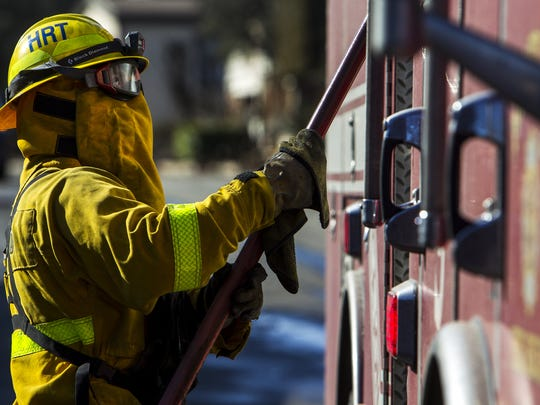 Austin Strand of Heartland Fire and Rescue puts back a fire hose after extinguishing smolders from the Lilac Fire in Rancho Monserate Country Club on Friday, Dec. 8, 2017 in Fallbrook, Calif. The fire is just one of several wildfires raging throughout southern California.
