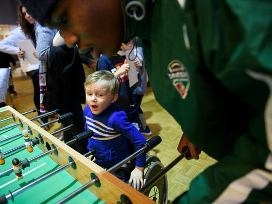 Wyatt Banks, 5, plays foosball with North Carolina high school player James B. Dudley at Shriners Hospitals for Children on Sunday, Dec. 10, 2017.