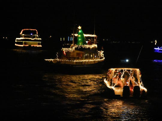Illuminated yachts reflect in the dark water. Despite the cancellation of the Christmas Island Style Christmas boat parade, a group of decorated vessels toured the Marco River on Saturday night.