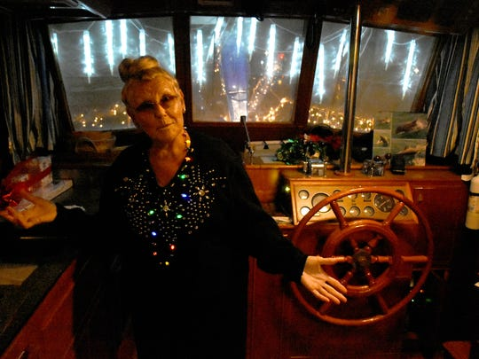 Aboard Grand Pelican, first mate Peggy Frazier exults on getting all the lights working. Despite the cancellation of the Christmas Island Style Christmas boat parade, a group of decorated vessels toured the Marco River on Saturday night.