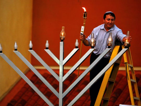 Shlomi Negri of Bonita Springs lights a 9-foot menorah at Coconut Point mall during last year's Hanukkah celebration.
