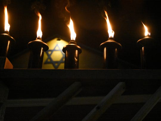 File: The ceremonial flames of the menorah burn in front of the Jewish Congregation of Marco Island