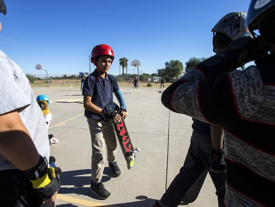 Ali Al-Shawi, 11, holds his new skateboard during Skate