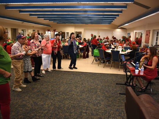 Partygoers sing and clap along with 'Feliz Navidad'