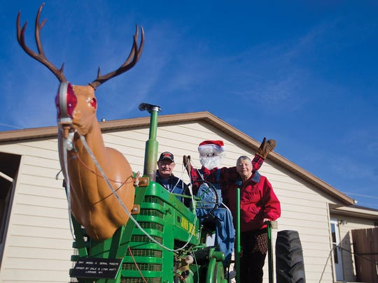 In this Dec. 13, 2017 photo, Dale and Lynn Hiatt stand on the back of their holiday-themed tractor in the front yard of their home in Laramie, Wyo.