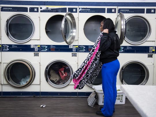 Jaznika Robinson folds laundry at Coin Laundry on Poinsett Highway on Wednesday, December 20, 2017.