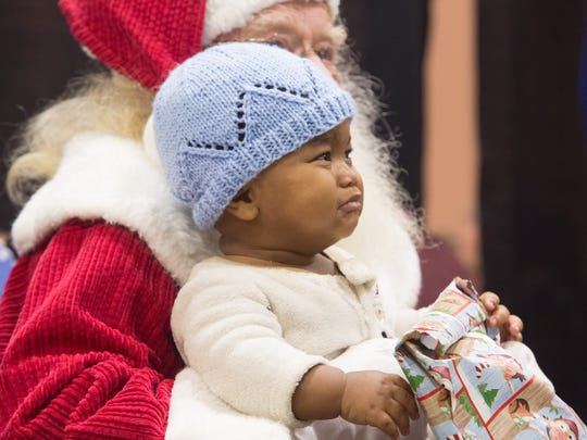 Majesty Thompson is apprehensive about sitting in Santa's lap at the Well in the Desert Christmas event, December 25, 2017.