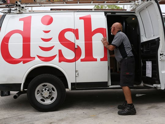 Alberto Rodriguez, a Dish Network technician, works around one of the company trucks on June 4, 2015 in Miami, Florida.