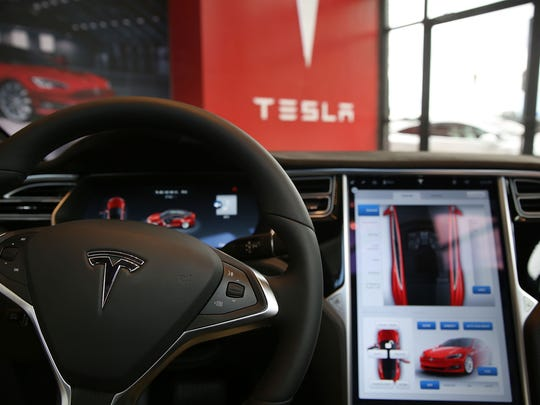 The inside of a Tesla vehicle is viewed as it sits parked in a new Tesla showroom. The electric car company and its CEO and founder Elon Musk have come under increasing scrutiny following a crash of one of its electric cars while using the controversial autopilot service.