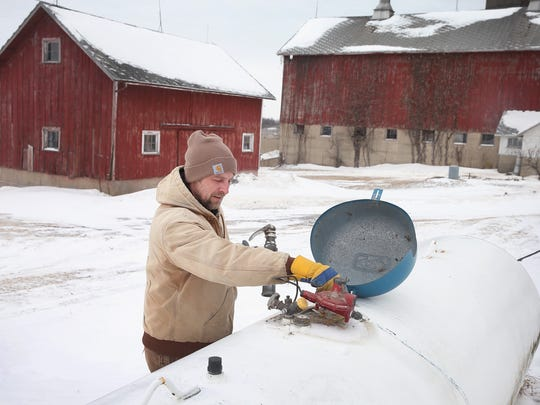 Mark Burger of Blackhawk Propane delivers propane to a farm house near Clinton. In 2014, a shortage of propane in the Midwest has caused prices to surge upwards to near $5 a gallon in some markets. The shortage is attributed to an unusually cold winter, increased exports, and a cold wet fall which forced many farmers use propane to fuel dryers for their crops.