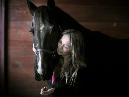 In a Dec. 5, 2017 photo, Tori Sue Olson shares a moment with her horse, Flit the Leader, while inside the stable where she boards him near Palmyra, Wis. Olson, who overcame a cocaine addiction and the loss of a close, father-like friend, nursed her horse Leader back to health after a life-threatening pelvic injury to become a National Barrel Horse Association World Championships finalist.