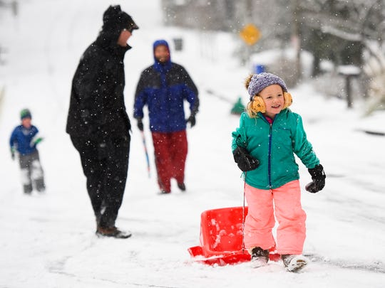 Sidney Park, 5, walks up Townes Street as she and others play in the snow in the North Main neighborhood on Wednesday, Jan. 17, 2018.