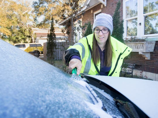 Whitney Fike scrapes ice off her car during freezing