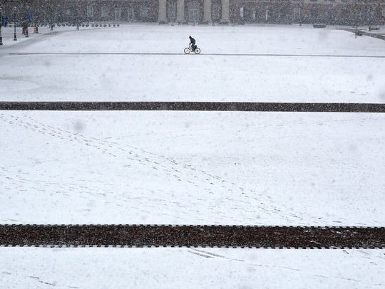 A bicyclist rides through the snow on the campus of