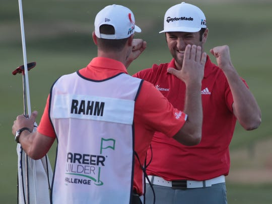 Jon Rahm celebrates with his caddy Adam Hayes after