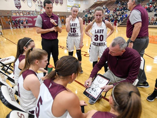 Assistant coach Steven Haile, back left, looks on as his father Jeff Haile talks to the Lady Colonel basketball team during a timeout as Henderson County plays Union County at Colonel Gym during the 2017-18 season.