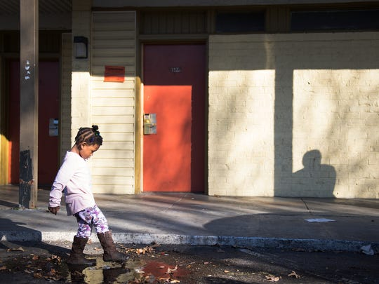 Shaniyha Hunter, 4, plays in a puddle at the Economy Inn as she waits for her mom to move their stuff on Thursday, January 25, 2018.