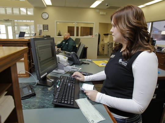 Veridian Credit Union loan officer Alison Swick processes checks at the credit union's EP True Parkway location in this file photo from 2011.