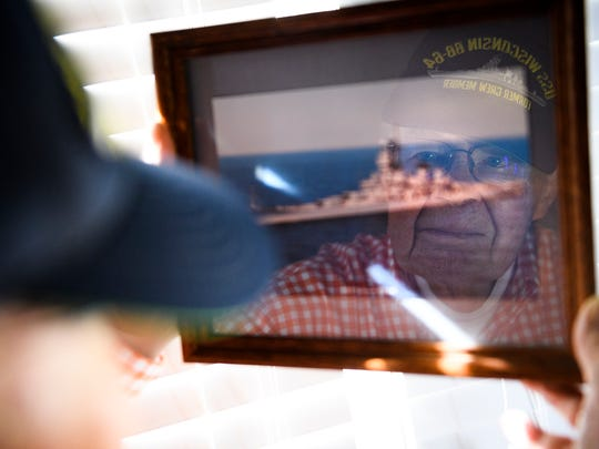 U.S. Navy veteran Leo Hofmeister poses for a portrait holding a picture of the USS Wisconsin in his home on Wednesday, Jan. 31, 2018.
