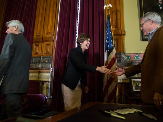 Kim Reynolds, Governor of Iowa, shakes hands and hands out pens after signing her first bill as governor, SF 512 which deals with water quality, on Wednesday, Jan. 31, 2018, at the Iowa State Capitol.