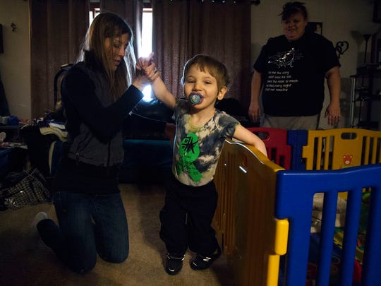 With the help of his physical therapist, Emily Tiedtke, four-year-old Tatum Woods, walks across his living room on Tuesday, Jan. 30, 2018, in Vinton.