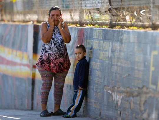 Mother Elizabeth Acevedo and her son Andres, 3, wait