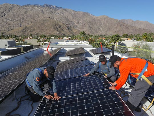 Renova Energy technicians, from left, Luis Banuelos, Jeff Flores, and Genaro Munoz install new solar panels on a home in Palm Springs, California on Feb. 6, 2018.