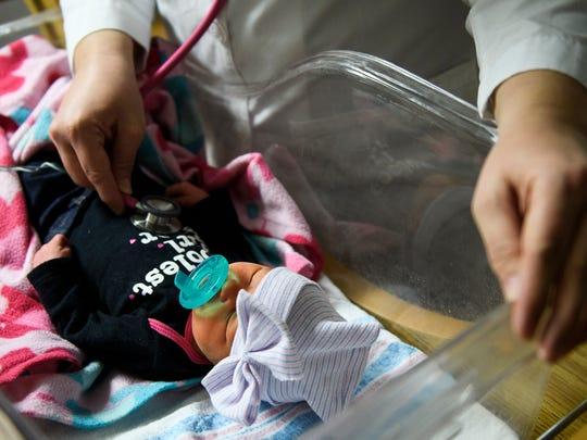 Dr. Jennifer Hudson checks a baby girl's heartbeat