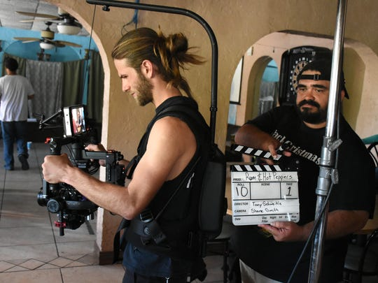 """Cinematographer Shane Smith readies his camera. A film crew has been shooting """"Rum and Hot Peppers"""" at locations in Collier County, including the Gators' Crossroads bar at Royal Palm Hammock."""