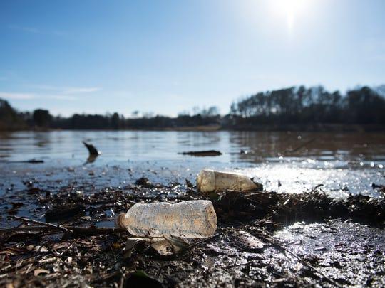 Garbage sits along the shore of Oak Grove Lake Park