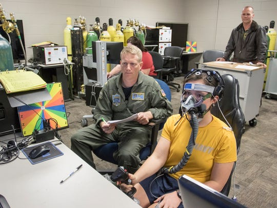 Navy Capt. Merrill Rice, top right, and Lt. Cmdr. Frank Bogni, left, observe as a student pilot flies a simulator during a study of pilot brain waves to help them avoid deadly hypoxia episodes at the Pensacola Naval Air Station on Thursday, Feb. 8, 2018.