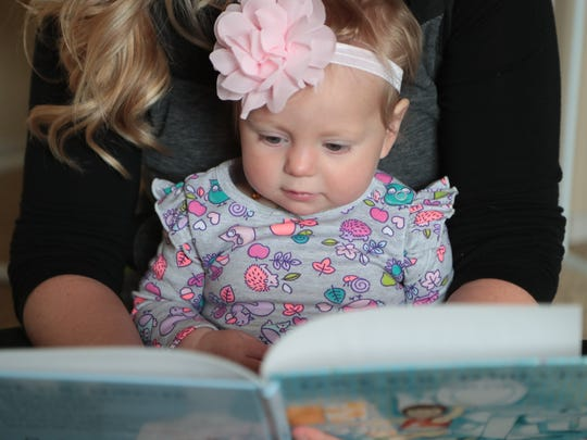 Ruthie Cody reads to her daughter Oakley during a break in her work day, January 30, 2018.