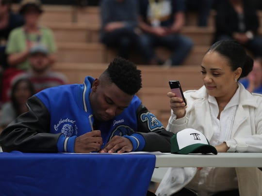 In a half-time signing ceremony football player James Green signs his letter of intent, Thursday, February 15, 2018.