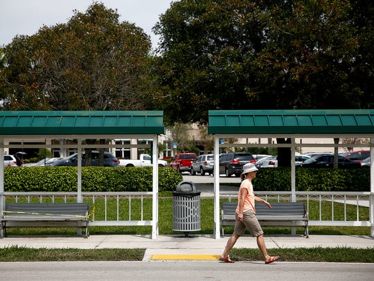 A pedestrian makes her way past a Collier Area Transit
