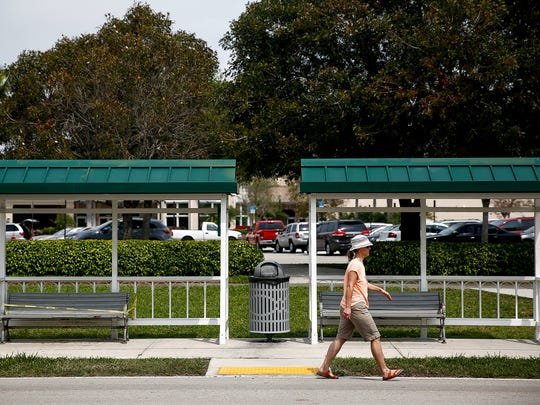 A pedestrian makes her way past a Collier Area Transit bus shelter on Fleischmann Blvd in Naples on March 23, 2015.