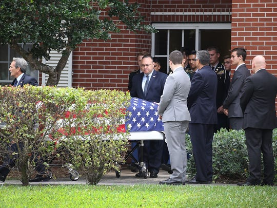 The flag draped coffin of Alaina Petty is taken out