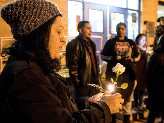 Wanda Madina of Asbury Park lights a candle. Mourners