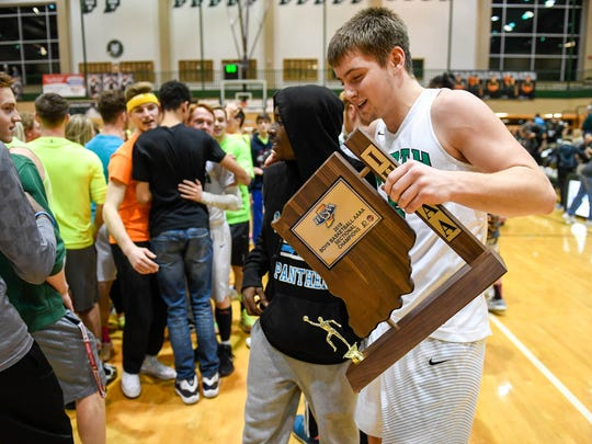 North's Ryan Huebner (5) carries the championship trophy as the team and fans celebrate winning the  Class 4A Sectional Championship at North Saturday, March 3, 2018.