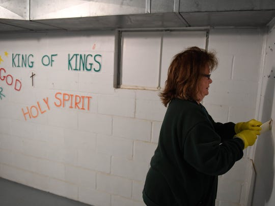 Thelma Skaggs works on a flood damaged classroom wall