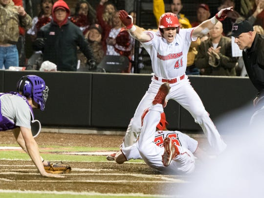 Daniel Lahare slides in past the tag as Gavin Bourgeois watches in UL's March 7 win over LSU.